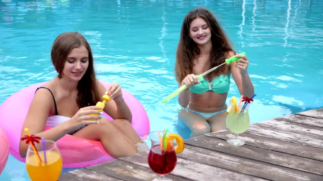 Cocktail party, girlfriends in swimsuits Blow soap bubbles in pool, company of Friends Relaxing in Poolside video