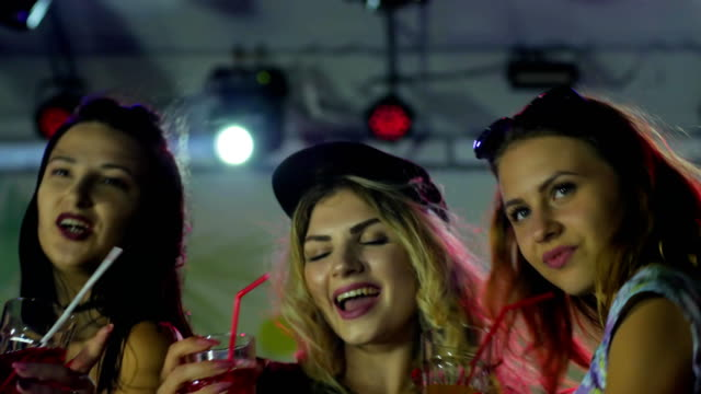 cocktail party, girls dance with beverage on party in lumiere lights, young women at disco club, lot female video