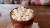 cocoa with marshmallows.man takes a spoon of cocoa with marshmallows video