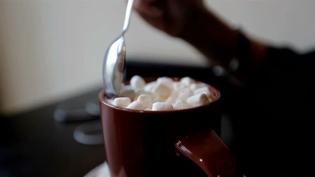 cocoa with marshmallows.women takes a spoon of cocoa with marshmallows video