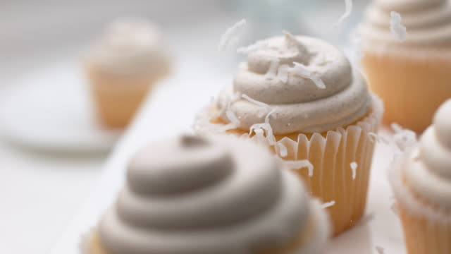 Coconut flakes falling onto cupcakes video