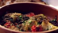 Cod and chorizo bake in earthenware dish, close up rack focus video