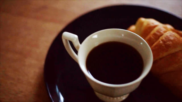 coffee and croissant on wood table video