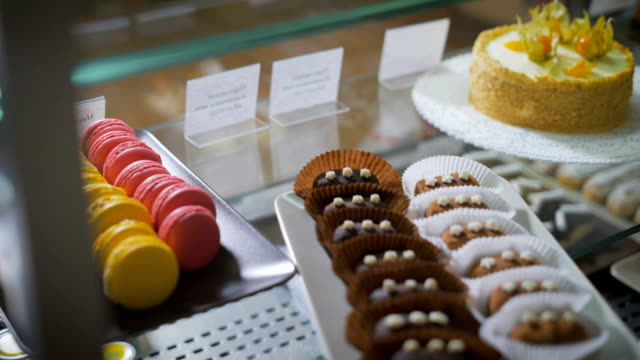 Coffee and pastry bar. Counter. On a glass surface desserts are exposed. On the right side multi-colored French macarons. On the left side tasty fruit cake. The employee of cafe exposes ready eclairs video
