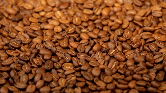 Coffee beans, a pile of roasted coffee beans rotating. Close up video