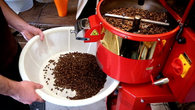 Coffee beans after roasting falling into a white basket. video