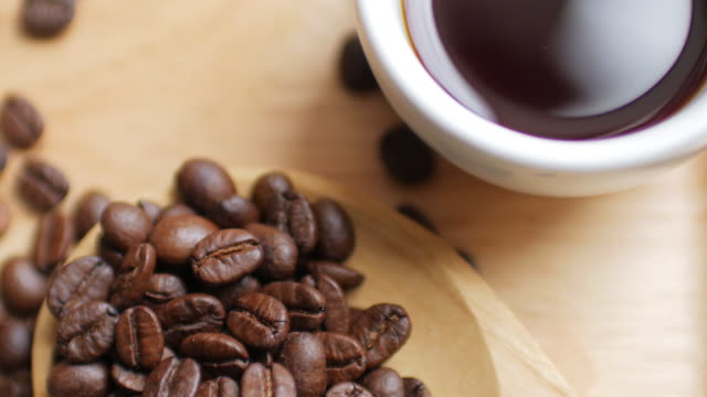 Coffee Beans and Hot Black coffee on Wooden dish on white table background , dolly shot left to right video