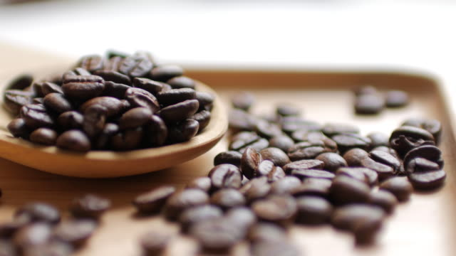 Coffee Beans and Hot Black coffee on Wooden dish on white table background , dolly shot tilt up video