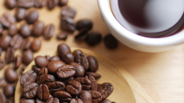 Coffee Beans and Hot Black coffee on Wooden dish on white table background , dolly shot right to left video
