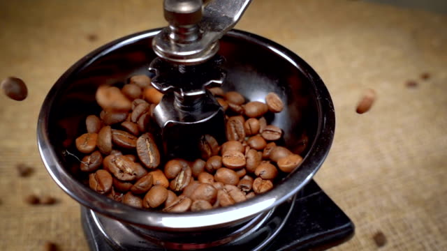 Coffee beans fall in the old grinder. Slow motion with rotation tracking shot. video