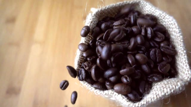 Coffee beans falling to sack in slow motion video