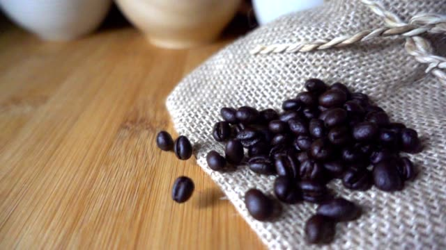 Coffee beans falling to sack on table in slow motion video