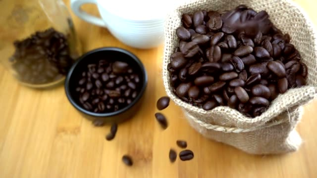 Coffee beans falling to sack - slow motion video