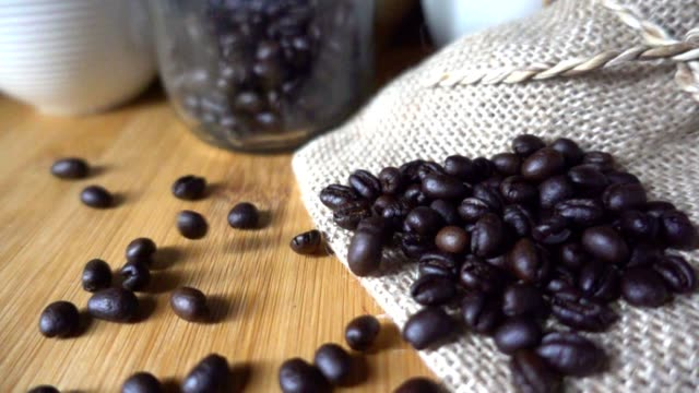 Coffee beans falling to table in slow motion video