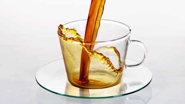 Coffee Being Poured in a Cup against White Background, Slow motion video