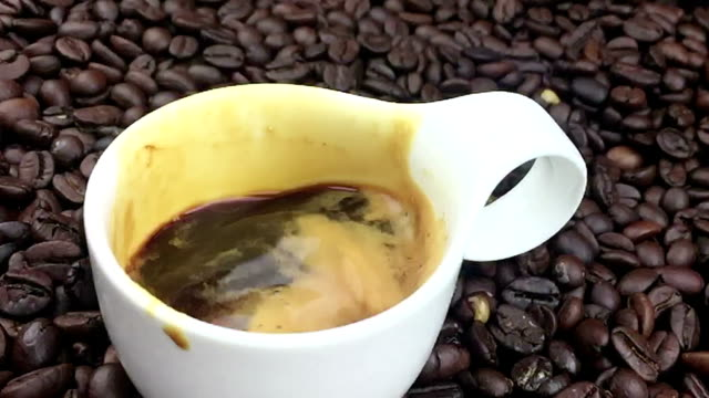 coffee drop falling in slow motion inside of cup of espresso italian coffee with foam on coffee beans background, food and drink and relax video