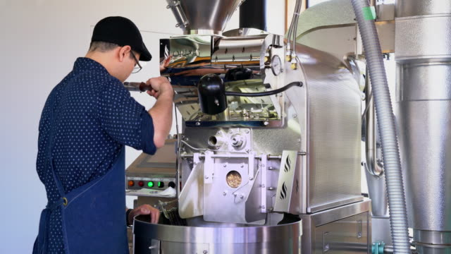 Coffee roaster smelling the beans to check on their progress video