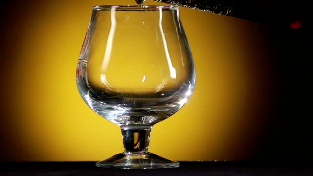 Cognac pouring from bottle into glass with splash on yellow background video