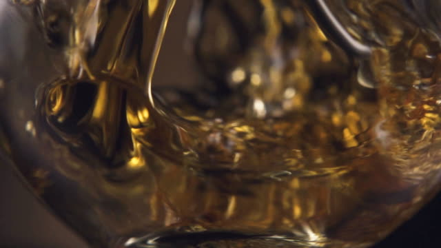 Cognac pours into a glass close-up. Slow motion video
