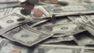 Coins falling on dollar bills, slow motion video