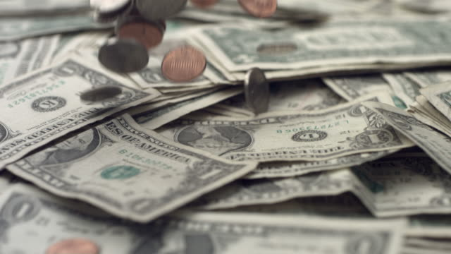 Coins falling on dollar bills, slow motion video