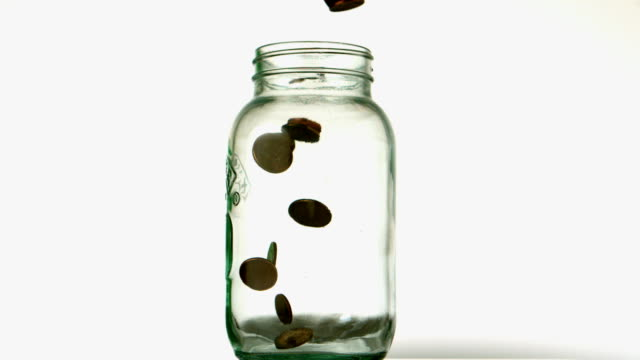 Coins pouring into glass jar on white background video