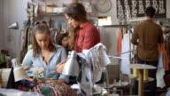 Colleague advises trainee machinist at clothes design studio video