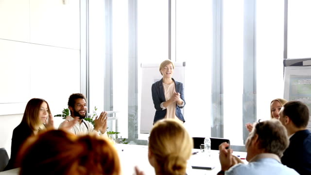 Colleagues applauding to their beautiful female colleague after presentation video