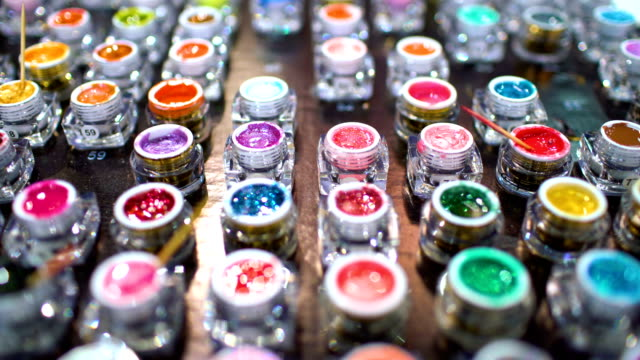 Collection of acrylic powder different colors for nails closeup. Shallow depth of field video