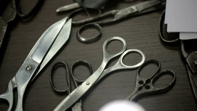 Collection of scissors on the table designer. Close up video