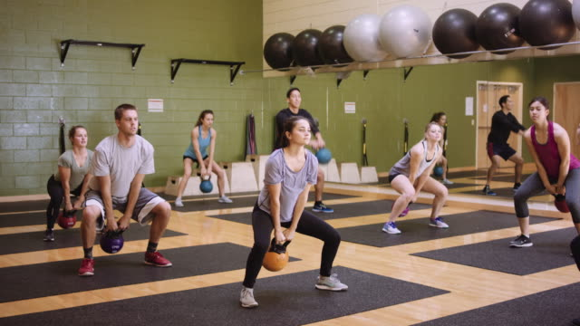 College age adults lifting weights fitness class video