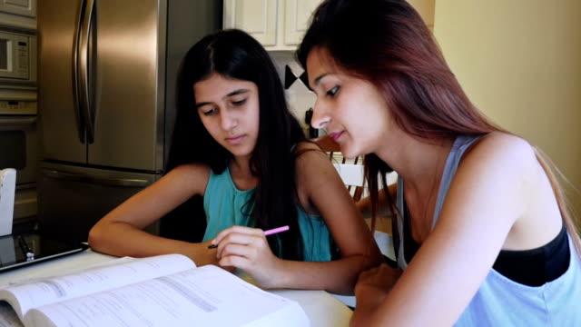 College age Hispanic girl tutoring preteen sister, helping with math homework video