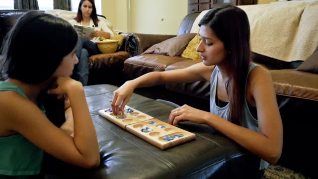 College age young woman playing board game with preteen sister video