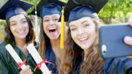 College friends make faces while posing for selfies after graduation video