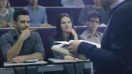College professor is teaching a class of multi-ethnic students while holding a book. video