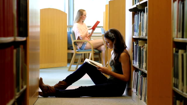 College Student Brunette Reads in Library WS video