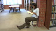 College student sitting on a stack of books video