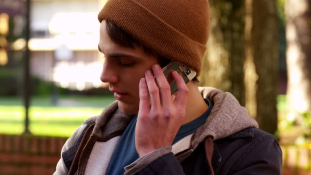 College student using cell phone outdoors in autumn video