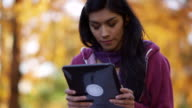 College student using digital tablet outdoors in autumn video