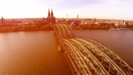 Cologne famous bridge aerial, German city Koln sight seeings Cathedral, during sunset. Opera and railway station, dramatic flight over travel tourist attraction Cologne bridge with trains and people video