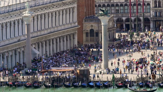 Colonnade building facing busy square with two columns, gondolas by riverbank video