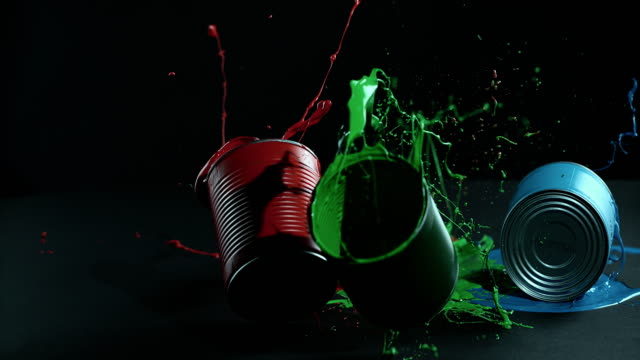 SLO MO color filled cans falling onto black surface video