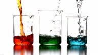 Colored chemicals pouring into beakers video