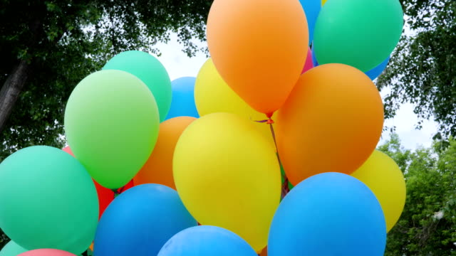 colored helium balloons, festive colorful air balloons associated bundle, swaying in light wind blow, holiday accessories video