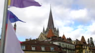 Colorful banners waving in wind, nice view of Lausanne Notre Dame Cathedral video