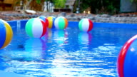 Colorful beach balls floating in pool video