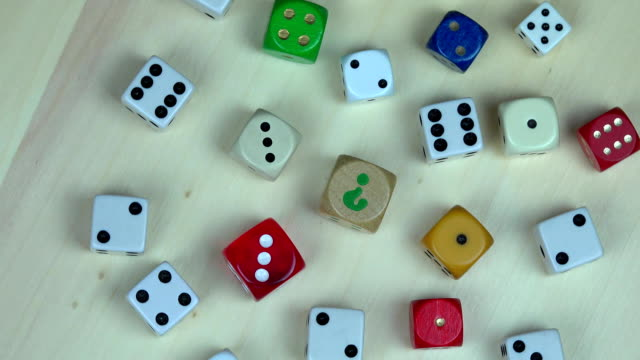 Colorful dices on wooden background. turntable anticlockwise video