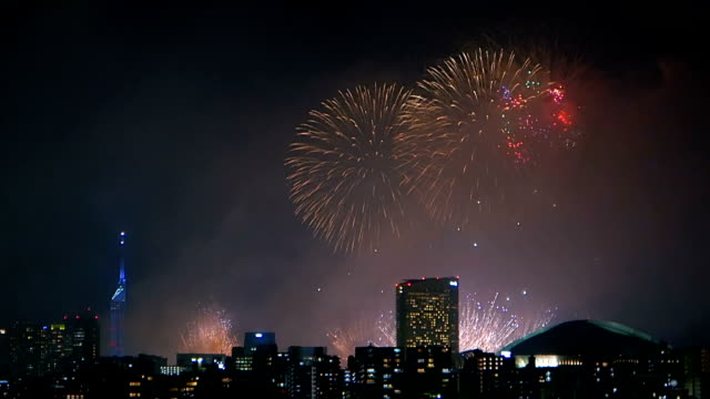 Colorful fireworks exploding in the sky of illuminated urban Fukuoka city. video