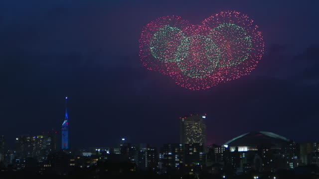Colorful fireworks exploring in the sky of illuminated urban Fukuoka city. video