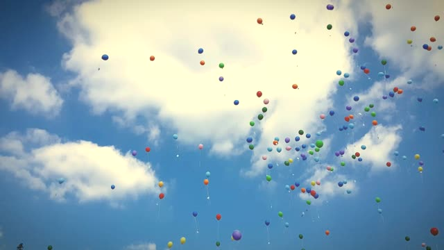 Colorful helium balloons flying up in the sky video